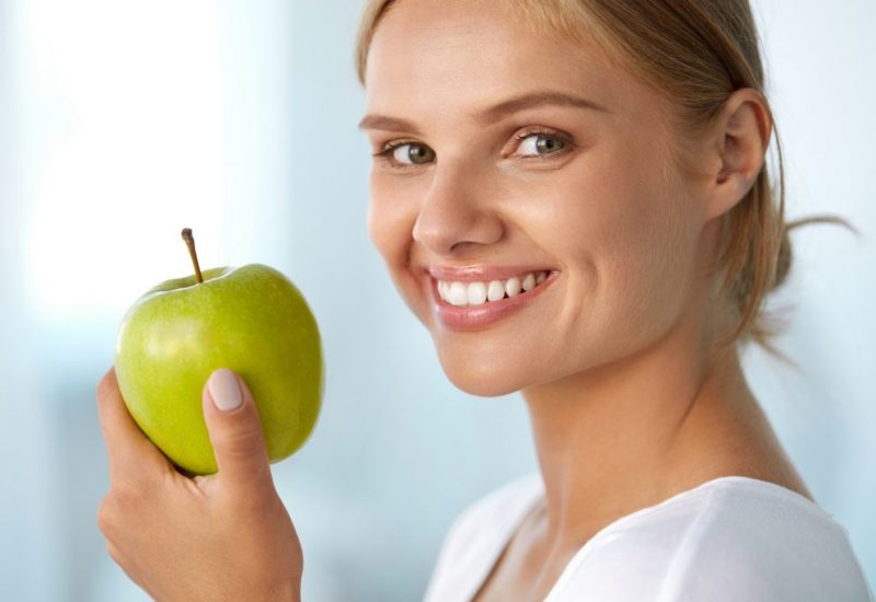 Woman With Apple. Beautiful Girl With White Smile, Healthy Teeth